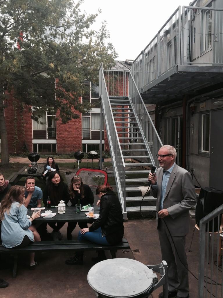 4. Maj Kollegiets efor, institutleder John E. Andersen, taler til håndværkere, ledere, bidragyder og alumner foran den midlertidige beboelsesby i haven ved rejsegildet 11. september 2015. Foto: FrederiksbergFonden.